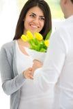 Homme donnant à bouquet des tulipes ses amies Images stock
