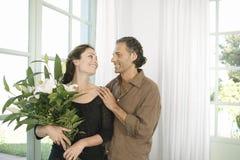 Homme donnant des fleurs à la femme. Image stock