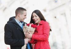 Homme donnant des fleurs à son amie ; jeunes, romantiques couples dehors Image libre de droits