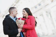 Homme donnant des fleurs à son amie ; jeunes, romantiques couples dehors Image stock