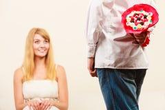 Homme donnant des fleurs de groupe de sucrerie de femme Amour Photographie stock libre de droits