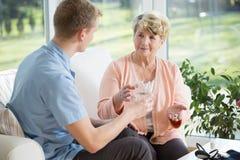 Homme donnant des médicaments à une femme plus âgée image stock
