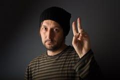Homme donnant deux doigts comme symbole de paix ou de victoire Photo stock