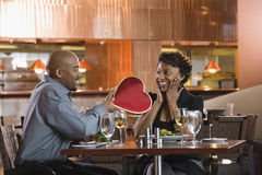 Homme donnant à femme le cadre en forme de coeur au restaurant Image libre de droits