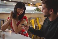 Homme donnant l'anneau à l'amie en café Photo stock