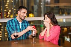 Homme donnant la bague de fiançailles à la femme au restaurant Image stock