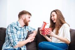 Homme donnant le boîte-cadeau à son amie heureuse Photographie stock libre de droits