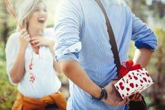 Homme donnant le cadeau de surprise en tant que présent à sa belle amie Photos libres de droits