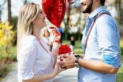 Homme donnant le cadeau de surprise en tant que présent à sa belle amie Image libre de droits