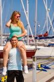 Homme donnant le tour de ferroutage d'amie sur la marina Image libre de droits