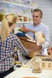 Homme donnant les articles non désirés à la boutique de charité Image libre de droits