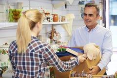 Homme donnant les articles non désirés à la boutique de charité Image stock