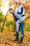 Homme donnant sur le dos la conduite à la femme en stationnement Photo stock