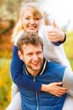 Homme donnant sur le dos la conduite à la femme en stationnement Photographie stock libre de droits