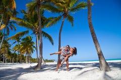 Homme donnant sur le dos le tour à l'amie à la plage des Caraïbes Images stock