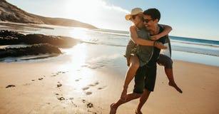 Homme donnant sur le dos le tour à l'amie sur la plage Image stock