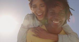 Homme donnant sur le dos le tour ? la femme sur la plage 4k banque de vidéos