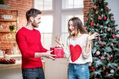 Homme donnant un cadeau de nouvelle année pour une femme à la maison photo stock