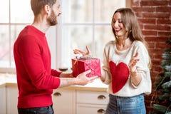 Homme donnant un cadeau de nouvelle année pour une femme à la maison images libres de droits