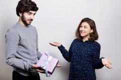 Homme donnant un présent à sa amie La surprise romantique, femme reçoit un cadeau de son ami Femme dans le looki étonné par amour Photo stock