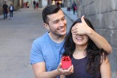 Homme donnant un présent à une femme magnifique photo stock
