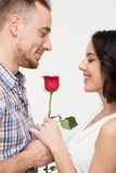 Homme donnant une rose au sien aimé Photographie stock