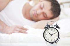Homme dormant avec l'horloge d'alarme Images stock
