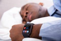 Homme dormant avec la montre intelligente dans sa main photos stock