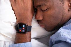 Homme dormant avec la montre intelligente dans sa main image stock