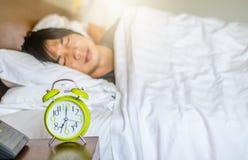 Homme dormant avec le réveil dans le premier plan Photos libres de droits