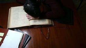 Homme dormant sur la vieille bible banque de vidéos