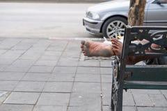 Homme dormant sur le banc de bord de la route Photographie stock