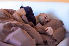 Homme dormant sur le lit Photos libres de droits
