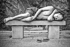 Homme dormant sur un banc images libres de droits