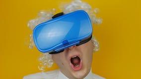 Homme drôle bouclé avec les cheveux blancs dans l'émotion de casque de réalité virtuelle, comique et gaiement humaine, sur le mur clips vidéos