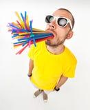 Homme drôle avec des pailles de jus en ses verres de soleil de port de bouche Images stock