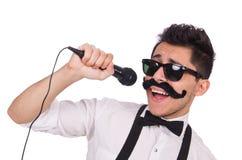 Homme drôle avec la MIC d'isolement sur le blanc Photos stock