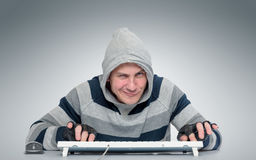Homme drôle avec un clavier devant l'ordinateur Image libre de droits