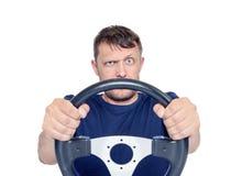 Homme drôle avec un volant d'isolement sur le fond blanc, concept d'entraînement de voiture photographie stock libre de droits