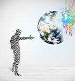 Homme drôle dans le costume de corps regardant la terre colorée d'éclaboussure Image libre de droits