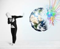 Homme drôle dans le costume de corps regardant la terre colorée d'éclaboussure Images stock
