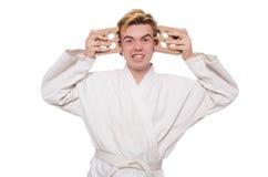 Homme drôle de karaté cassant des briques d'isolement Image stock