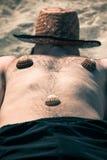 Homme drôle dormant sur la plage Photographie stock libre de droits