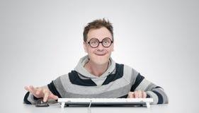 Homme drôle en verres avec un clavier devant l'ordinateur Image stock