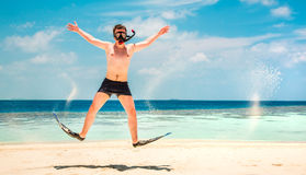 Homme drôle sautant dans les nageoires et le masque. Photographie stock libre de droits