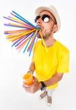 Homme drôle tenant un verre des verres de soleil de port de jus et du T-shirt jaune sur le blanc Images libres de droits