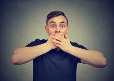 Homme effrayé avec des mains couvrant la bouche regardant impatiemment l'appareil-photo photos stock