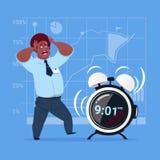 Homme effrayé d'affaires d'Afro-américain avec le concept de gestion du temps de date-butoir de réveil Images libres de droits