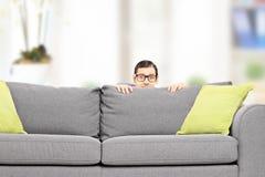 Homme effrayé se cachant derrière un sofa Photos stock