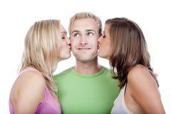Homme embrassé par deux filles images libres de droits